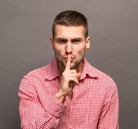 shushing: Man making a shushing gesture with his finger to his lips and asking for silence isolated on grey background.
