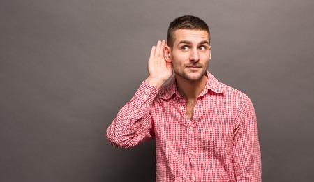 Écoute mâle tient sa main près de son oreille sur fond gris. Bel homme essayant d'écouter la conversation de quelqu'un.