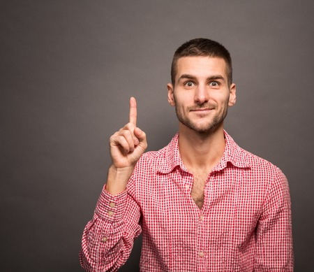 Excited man pointing a great idea over grey background. Short-haired man in pink shirt looking at the camera.