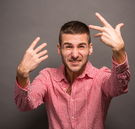 attitude boy: Close-up portrait of angry upset young man with his hands in air. Man with serious glance isolated over grey background. Stock Photo