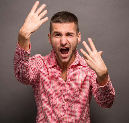 attitude boy: Handsome young man with his hands in the aietrying to show something. Short-haired man with opened mouth yelling isolated on grey background. Stock Photo