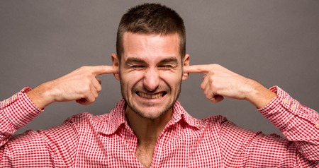 deafening: Close-up portrait of young angry unhappy stressed man covering his ears and closing his eyes in studio.