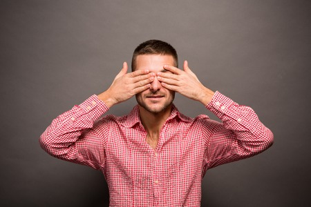 hands covering eyes: Young attractive male covering eyes with his hands, studio shoot isolated over grey background. Stock Photo