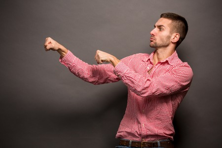 attitude boy: Handsome young man posing in profile and keeping his hands in the air trying to explain something. Stock Photo