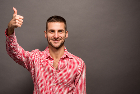 thumbup: Young casual man giving thumb-up over grey background. Happy man smiling and posing for photographer. Stock Photo