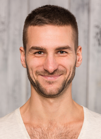 men standing: Close-up portrait of young handsome man posing in studio for photographer. Man in white T-shirt smiling for the camera.