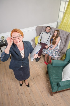 demanding: Frightened couple with problems on reception for family psychologist. Strict and demanding psychotherapist has a shock about them. Stock Photo
