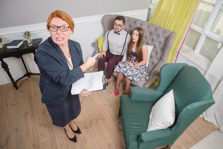 problemas familiares: psicoterapeuta de pelo rojo que muestra al par que se sienta en el sofá. La gente tiene problemas familiares graves.