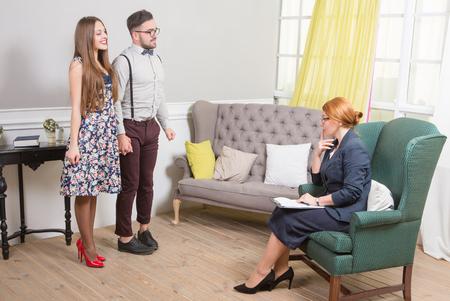 problemas familiares: hermosa joven pareja de pie en frente de la psicoterapeuta y contando sus problemas familiares. Foto de archivo