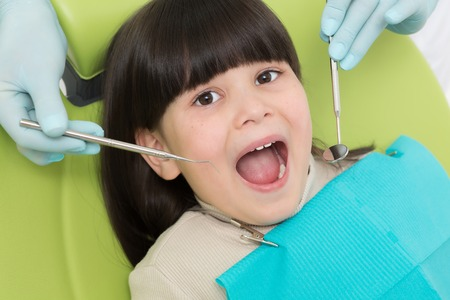 mouth opened: Little brunette lady having her teeth examined by professional dentist. Lady sitting with her mouth opened.