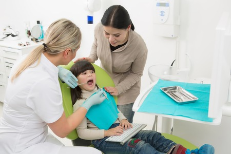 dentists surgery: Dentists surgery concept. Young girl having check up at dentists surgery while her mother standing near by her. Stock Photo