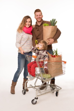 cart: Happy couple holding grocery shopping bags while their little baby sitting in shopping cart isolated on white background.