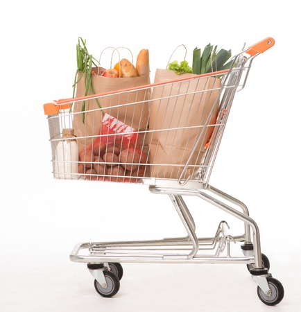 bagged: Shopping concept. Shopping cart filled with bagged groceries shot on white background.