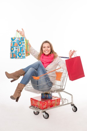 woman shopping cart: Happy woman in shopping cart holding multi-coloured bags. Blond woman posing in cart over white background after shopping.