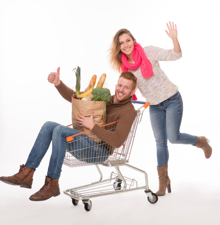 okey: Happy man lying in shopping cart, holding bags with groceries and showing okey sign. Cheerful lady pushing shopping cart. Stock Photo