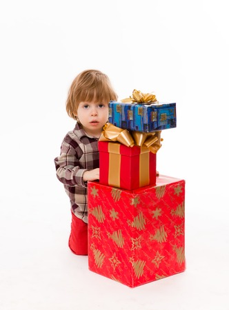 waiting glance: Beautiful little baby hiding behind presents over white background. Baby with serious glance waiting for Santa Clause. Stock Photo