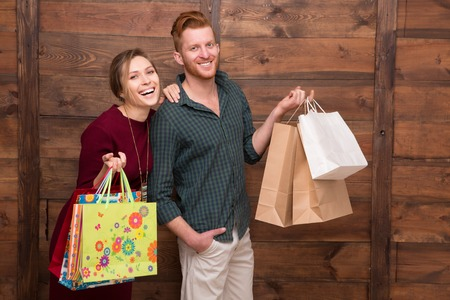 ner: Happy smiling lady standing ner her boy-friend over wooden background. Happy couple posing with shopping bags.