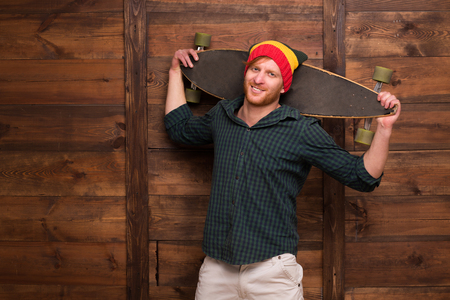 skater boy: Hipster man in hat holding skateboard over wooden background. Professional skateboarder is going to perform.