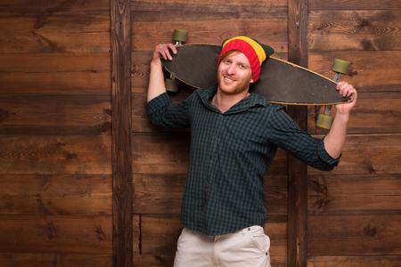 ni�o en patines: hombre inconformista en que sostiene el monopat�n sombrero sobre fondo de madera. skater profesional se va a realizar.