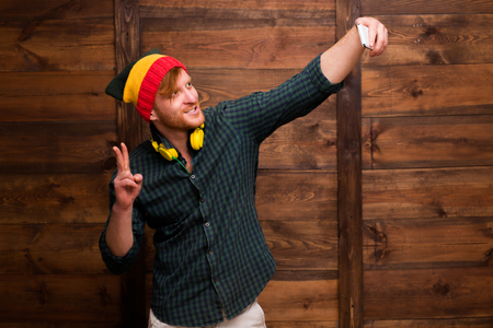Hipster man making selfies over wooden background. Handsome man showing yo sign and smiling for the camera.