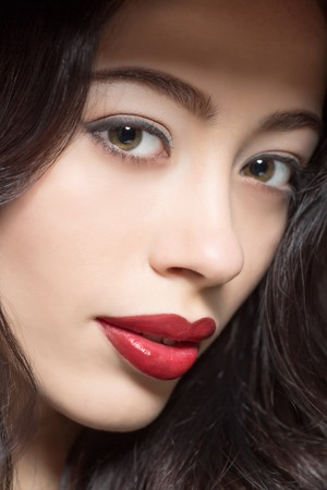 sexy glamour: Close-up portrait of fashion lady with dark red lips and perfect make-up looking at camera in studio.