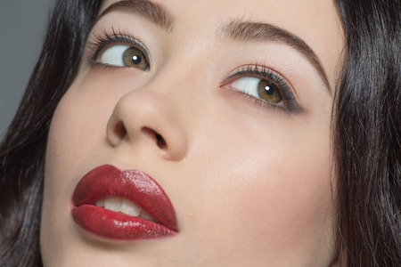 fashion magazine: Portrait of fashion lady posing for fashion magazine or catalogue and demonstrating her dark red lips in studio. Stock Photo