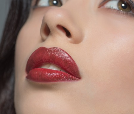Close-up portrait of fashion or vogue lady posing for fashion magazine or catalogue and representing her beautiful dark red lips in studio. Фото со стока - 53786672