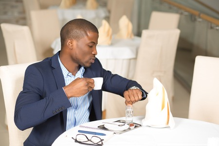llegar tarde: El hombre de negocios beber café y mirando su reloj con el fin de no llegar tarde a otra reunión de negocios.