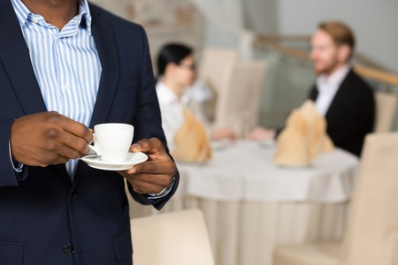 navy blue suit: Close-up of businessman in navy blue suit holding cup of coffee while his colleagues communicating at table behind him. Stock Photo