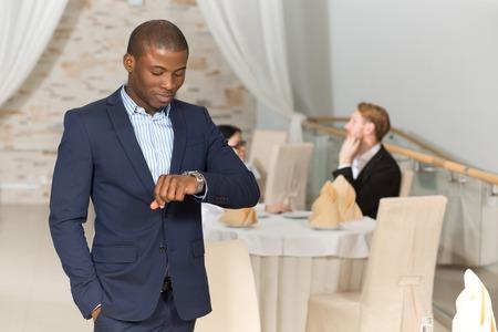 Hadsome de negocios asiático en traje de negocios mirando su reloj con el fin de no llegar tarde a la próxima reunión de negocios.