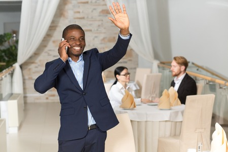 navy blue suit: Handsome businessman in navy blue suit waving to someone and speaking over mobile phone while his foreign collegues sitting at table and communicating. Stock Photo