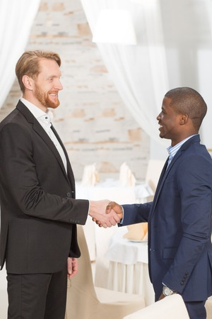 come in: Business people shaking hands and standing face to face. Two businessmen trying to come to agreement in restaurant.