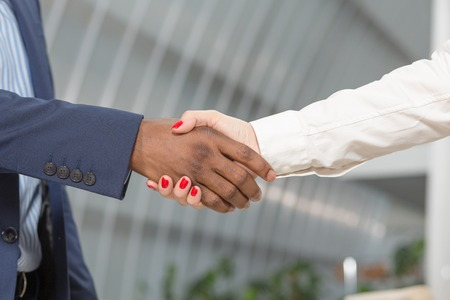 pacto: Business people shaking hands outdoors. Close-up of man and woman having handshaking in front of business office.