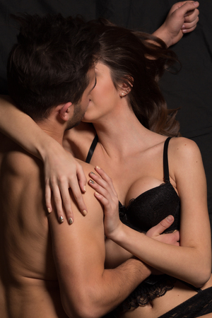 young couple sex: Close-up portrait of sexy young couple body at night: kissing, holding hands. Romantic atmosphere over dark background.