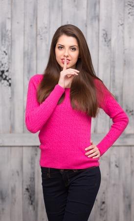 Ritratto del modello donna bruna in pullover rosa che chiede il silenzio nemico in studio. Signora felice con i capelli lunghi tenendo una mano sul fianco.