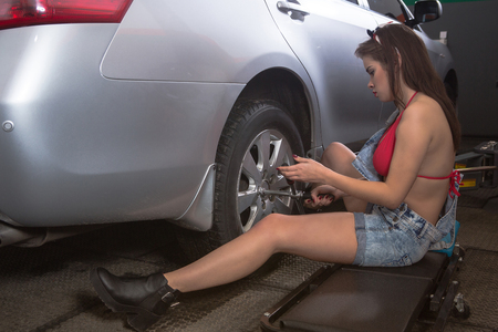 torque wrench: Mechanic, a young woman changing the front tire of a black sedan using a torque wrench in a tire service center garage