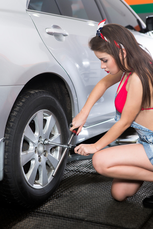 tiring: Portrait of young lady in jeansshort and red underwear tiring at auto service station. Beautiful lady repairing automobile. Stock Photo