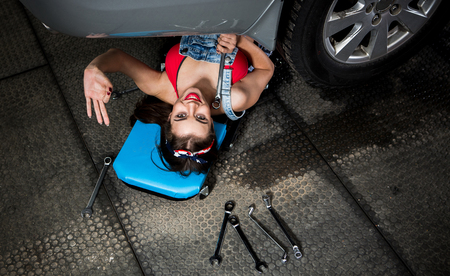 Young woman solving car problems while lying under car and fixing it in garage. Beautiful lady showing okay sign.