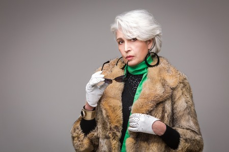 Portrait of senior rich woman holding sunglasses in front of her. Vogue lady in fur coat posing in studio isolated on grey background. 免版税图像