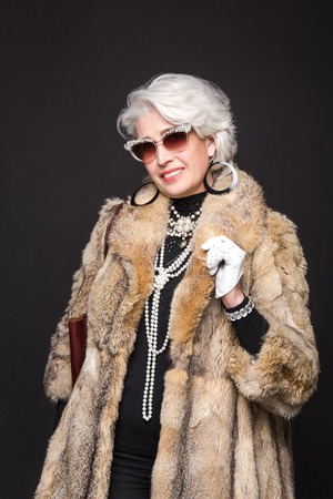 Senior rich woman with blond hair smiling for camera and posing in studio. Happy woman wearing expensive fur coat and sunglasses.