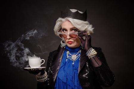 rica mujer mayor que tiene una taza de té como la reina Isabel de Gran Bretaña. Hermosa anciana en ropa cara aislado en negro. Foto de archivo