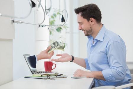 pagando: Feliz hombre de negocios sentado delante del ordenador portátil mientras que una mano que sostiene cientos de billetes de dólares a través de concepto de la pantalla del ordenador portátil para el e-comercio por Internet, pago y banca electrónica. Foto de archivo