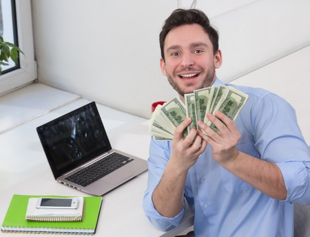 Handsome male freelancer holding many dollars in front of him and smiling for camera while working near laptop computer.