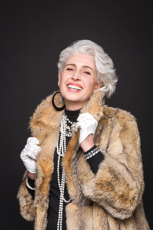 donna ricca: Portrait of senior rich woman in expensive fur coat happy smiling for photographer. Beautiful woman toothy smiling.