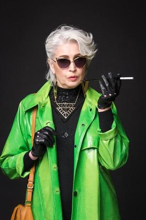 Portret van senior rijke vrouw in fel groene jas dragen van een zonnebril terwijl sigaret in de voorkant van haar geïsoleerd op een zwarte achtergrond.