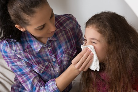 Fever, cold and flu concepts. Sick child wiping or cleaning nose with tissue while her mother helping her.