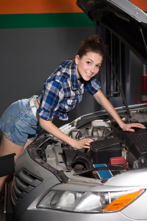 diagnosing: Younf worker lady in sexy clothes diagnosing engine or motor and looking at camera. Happy woman looking at photographer.