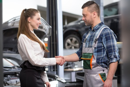 two car garage: Customer woman having handshake with mechanic man at repair shop. Businesswoman is satisfied with her automobile. Stock Photo