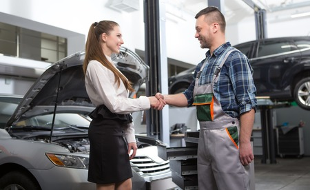 auto repair: Professional auto mechanic and woman having handshake in auto repair shop. People standing face to face and smiling.