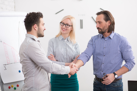 deal in: Happy business executives having deal in office. Business people finishing their communication by shaking hands. Stock Photo